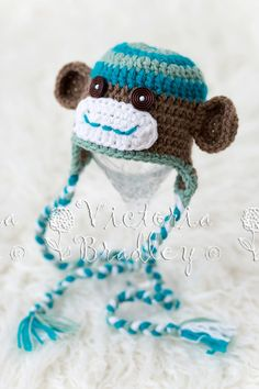 Really cute sock monkey hat with ear flaps and braided tassels!    Great aqua blues with brown!    Made from soft baby acrylic yarns.    Hand