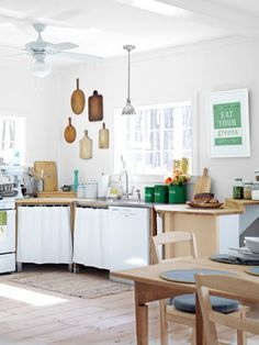 Light Filled and Clutter-Free ~ Skip upper cupboards in favor of an open and airy kitchen. A Haley & Lucas print reminds diners to eat their veggies.