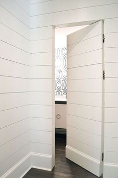 Either Orr - hall paneled in tongue & groove paneling frames hidden door, Antonina Vella Dolce Vita wallpaper