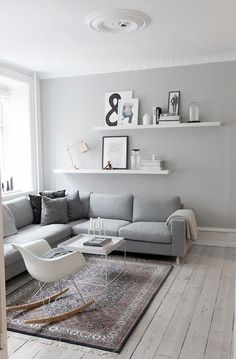 Inspiration for a light-grey themed living room or lounge. You just need a light grey sofa, some grey paint, and some white accents like shelves, chairs, and artwork.