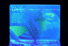 US. Passports under black light — intricate designs exposed under UV (ultraviolet) light.