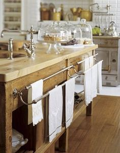 'The vintage French towel racks, which Susan Dossetter added to the antique baker's table, are hung with vintage towels that she has collected over the years. The baker's table came with a new sycamore top. Vintage and new cake plates hold treats .'