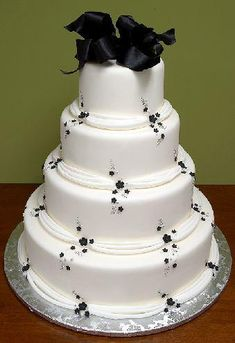 White tier cake with delicate black accents and topper