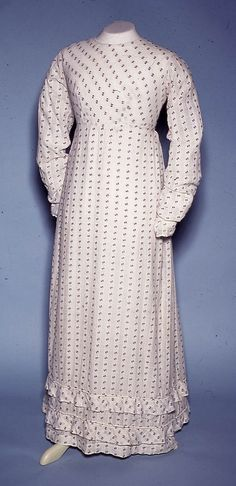 Day dress of white cotton woven with a figured design in lilic and open weave stripe. The front bodice is bais cut and darted to give a smoother and tighter fit over the bust, fastening at the back with Dorset thread buttons and a tape at the waist. The skirt was a gored section at each side, but still flat at the waist, and gathered only at the back. Size: Length back: 133 cm. c.1815