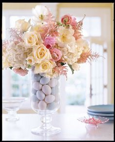 Artificial eggs surround a water-filled glass in the middle of the vase. Complete Instructions: Flower arrangement in glass vase with eggs: Place artificial eggs in the bottom of a tall, wide vase. Place a tall glass in the center of the vase, making sure there is enough room between the two for additional eggs. Insert eggs around the glass until it is fully hidden. Carefully pour water into the glass and arrange a bouquet of white hydrangea, white roses, white tulips, and pink astilbe.