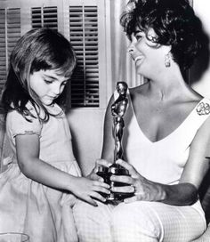 """Elizabeth Taylor with her daughter Liza Todd and her Oscar for """"BUtterfield 8"""" 1960."""