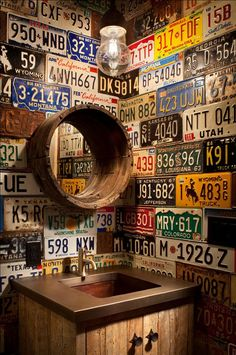 Vintage license plates cover the walls of a powder room in a rustic-style ski lodge. This obviously took a lot of time and care to plan and install.