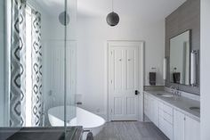 Gray and white ikat curtains soften the vibe of this chic contemporary bathroom. Overhead, the round dark gray pendant light brings further geometric visual interest to the space.