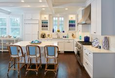 Lit glass-front cabinets offer a stunning focal area for colored glassware. A large island provides ample prep space for the chef and extra seating for hungry guests.
