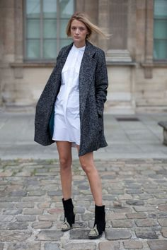 A crisp white dress gets the fall treatment in Balmain booties and a proper coat.
