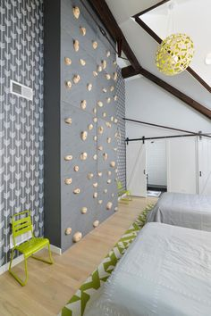 Welcome to the bedroom every kid (and many a grown up) dreams of having. Decked out in cool contemporary style, the space features a gray and white palette with graphic print wallpaper, bold lime green accents and—wait for it—a climbing wall.