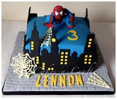 "8"" spiderman cake with hand cut buildings and sugar model. the webs are made from chocolate and his name is handcut using the spiderman font"