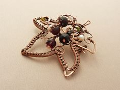 """Brooch """"Currant"""" of copper and glass."""