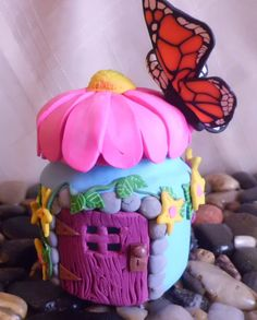 This one of a kind, whimsical, fairy home is handmade using polymer clay applied to a baby food jar. A butterfly has stopped to rest on the flower