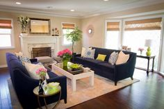 Navy sofas facing one another create an intimate conversational area, while an elegant marble fireplace stands as the focal point in this transitional living room. Fun colors and playful use of pattern stand out against neutral walls and create a cheerful space that's comfortable and welcoming.