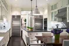 Contemporary white kitchen design with creamy white ivory kitchen cabinets, honed black granite countertops, white island pendants, pot filler, white vinyl dining chairs with nailhead trim and glossy wood dining table. Kitchen Remodel, Kitchen Design, White Modern Kitchen, Ivory Kitchen Cabinets, White Kitchen Design, New Kitchen, Kitchen Interior, Dream Kitchen, Ivory Kitchen