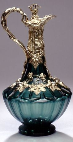 "Reily & Storer Type/Style:Colored  Emerald green and silver mounted decanter with detachable ""Claret"" label by Reily & Storer, London, 1844. The large detachable vine leaf centered on the shoulder below the spout is pierced with the word ""Claret"" and as a separate piece is fully hallmarked. One suspects that the jug was originally supplied with a variety of interchangeable labels such as ""Hock"", ""Madeira"", ""Port"" and ""Burgundy"". Ht. 12""."