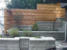 retaining wall idea for side yard.   Cinder blocks to match fireplace with horizontal wooden fence