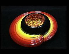 """Vitrix and GlassMaster Thomas Kelly's latest creation, Solar Geode in Black Sunburst. A blown glass black bowl with colorful geode looking glass frit melted to the inside, wrapped with five ropes of molten colored glass. Approximately 12"""" x 5"""". Artist signed and dated, highly collectible."""