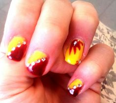 Sunny summer nail art: red and yellow give the warmth of the season and three or four strass make it shine like the sun. DIY