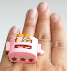 A super pink toaster with strawberries on it and a strawberry toast in it!!     It measures approx. 0.85 inch wide and 1 inch high is on a silver plated adjustable bang that will fit most ring sizes.