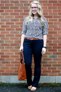 Navy bootcut slacks paired with a print blouse and flats - Franish