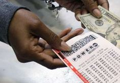 FILE - In this Jan. 13, 2016 file photo, a clerk hands over a Powerball ticket for cash at Tower City Lottery Stop in Cleveland. Powerball estimates that its jackpot for the May 4, 2016, drawing is $348 million.
