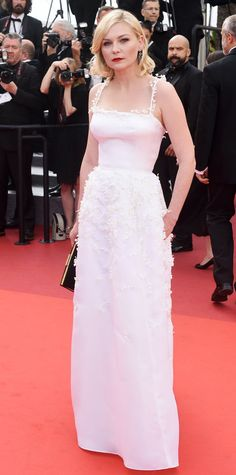 Kirsten Dunst swept the red carpet during the Loving premiere at Cannes in a stunning white silk Dior Haute Couture pillar gown that featured a cascade of lily of the valley embroidery. A cherry-red lip and a black gold-rimmed clutch played up the contrast nicely.