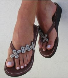 This pretty sandal has three small beaded flowers runing down the outer side of the sandal. It has a tan leather upper and a soft padded sole giving you extra comfort with a small wedge heel (1.5 inches 3.8cm) which makes it perfect for a day to day run about. Wear them to add a haute-hippie element to patterned shorts and oversized shades.      Genuine Leather Upper (dyed & sun dried)    Small wedge heel - 1.5...