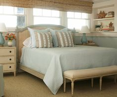 "Beachside Retreat  With plenty of textures and natural light, this cozy bedroom implies a ""by-the-sea"" locale. Soft blue walls and bedding are complemented by warm off-white trim and furniture, recalling the colors of sand surf & sun. A woven window shade incorporates natural texture cozy bedroom creates the perfect oceanside vibe without going overboard. Subtle accents such as starfish seashells and wicker convey a beachy style without being too themed driven"