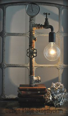 steampunk industrial feel * made with old books, lights, pipes & faucet pieces.