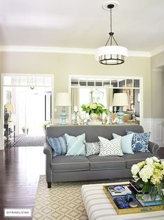 Elegant, open concept living room, with with grey sofas and drum shade pendant lights create a neutral backdrop of layers of beautiful blue patterned pillows and blue and white pottery. Decorated for Summer with fresh cut greenery, hydrangeas and palms. An upholstered striped ottoman is a classic piece in any setting.