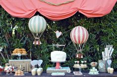 Travel party with vintage hot air balloons, luggage props, bustled fabric curtain w/sisal rope detail, map wrapping paper, fluffy cloud-like buttercream cake, and goodies like cloud meringue, chocolate hot air balloons...