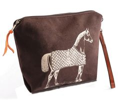 """Rebecca Ray Burghley Brown Horse Pouch. Made of heavy cotton duck exterior decorated with vintage equestrian line art. Coordinated with the Burghley totes. Use for cosmetics or great for all your tech accessories. Has a handy leather wrist strap so you can use alone as a clutch. Gusseted bottom with zippered top. From Rebecca Ray designs, made in the USA. • 9"""" x 11-1/2"""" x 1""""."""