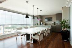 No projeto desta varanda gourmet, a designer de interiores Liliana Zenaro eliminou a churrasqueira e a coifa. No lugar desses elementos, a profissional optou por instalar um forno elétrico, uma adega e um frigobar. No ambiente, a bancada de trabalho foi acoplada à mesa de jantar em laca branca