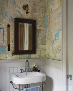 In this guest bath, a Duravit sink with Dornbracht fittings in a guest cottage bath, which is papered with old AAA maps; the wainscoting is painted in Farrow & Ball's Cornforth White.  Tour the entire home.