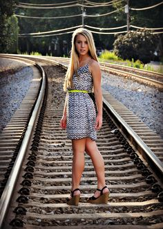 Girl poses on train tracks.  She walking down tracks and then turns and looks great.