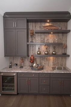 love the cabinet color and wood bksplsh a gray home bar with open shelving and rustic paneling as a backsplash the bar includes a wine fridge