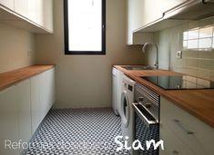 reforma de una cocina pintada, con materiales y colores nobles (encimera de madera, azulejos brillo con dibujos de molinillos en negro y sobre encimera verdes, muebles blancos sin tiradores. Generando un espacio cálido y suave.