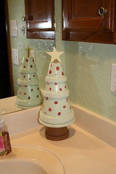 Cute tree made from terra cotta plant holders and painted.   Bigger and put on the porch??