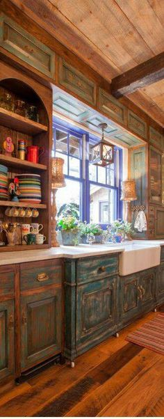 love the distressed cabinets and colorful plates on open shelves