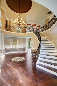 Grand entry round staircase with elegant chandelier.
