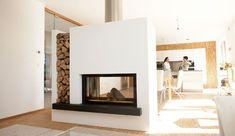 Durchsichtkamin als Raumteiler mit Holzlege: