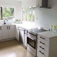 @iamtarryndonaldson on Instagram Herringbone tiled kitchen splashback with black handles and tape are in a white on white space softened with light wood flooring