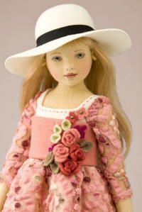 Maggie Iacono  Blonde doll in rose floral dress with flowers worn on top portion of dress.