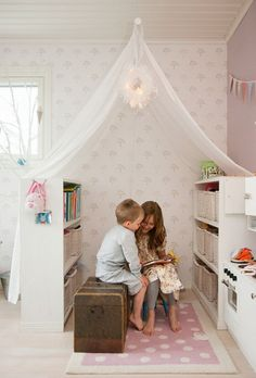 A reading nook in the corner of a bedroom made with 2 low shelves, rug, net and a pretty light fitting. Simple and very effective!  www.homeology.co.za