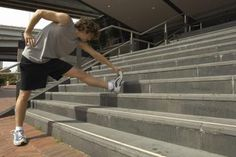 A man is stretching his legs on an outdoor staircase.