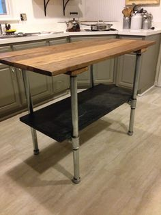 Reclaimed Barn door made into a kitchen island with a soapstone shelf and galvanized pipe!