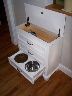 Old nightstand dresser repurposed into a dog feeding station.
