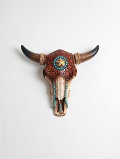 The Tandy, our faux tooled leather natural bone resin long horn skull, is custom finished in a natural cognac leather, turquoise resin stone, gold star and jute wrapped horns. This faux longhorn skull can match any style of hanging wall home decor. Unlike our other bison skulls, this beautiful piece has a large amount of detail including tooled detailing on the forehead of the skull piece. This western decor cow skull is perfect for the home or office!  Dont want her in natural? We can…